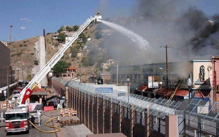 Пожарные из Аризоны, США, помогают мексиканским коллегам тушить пожар через пограничную стену.