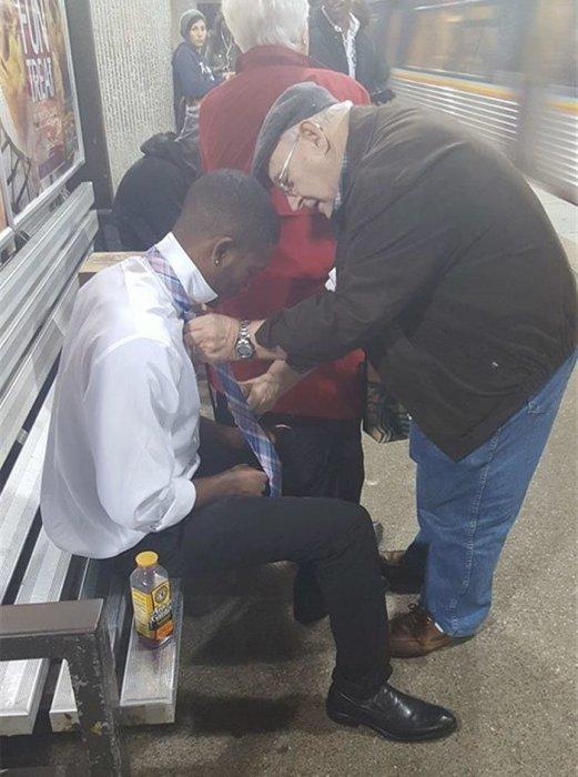 Пожилой мужчина помогает совершено незнакомому ему парню завязать правильно галстук.
