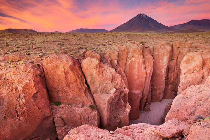 Стратовулкан находится в Чили, его высота над уровнем моря — 5920 метра.