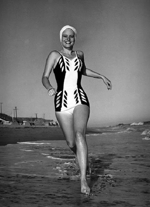 Спортсменка, бегущая по кромке воды.