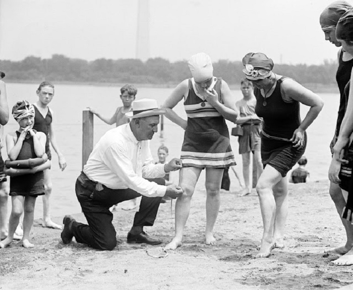 Полицейский измеряет расстояние от края купальника до колена.