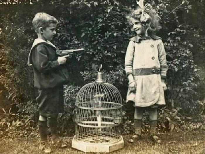 Мальчик наставил пистолет на девочку, которая смеется.
