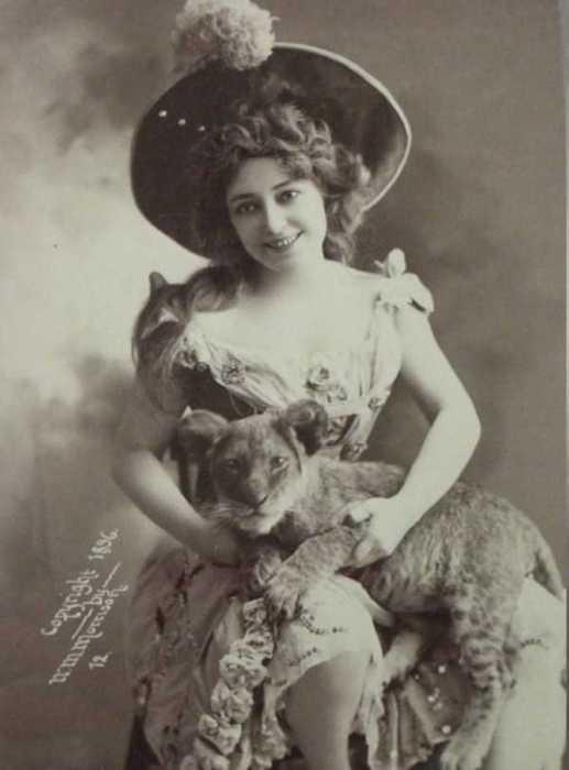 Старый снимок девушки, которая держит львенка на руках.