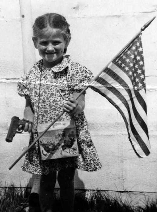 Шестилетняя девочка с американским флагом и пистолетом в руках.