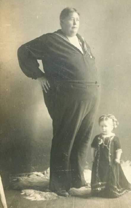 Огромных размеров моряк рядом с малюсенькой девочкой.