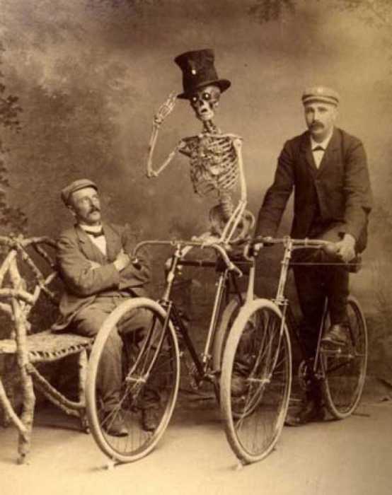 Скелет в цилиндре на велосипеде отдающий честь.