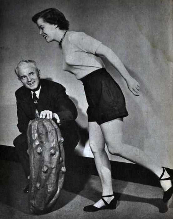Девушка имитирует прыжок через макет огурца.