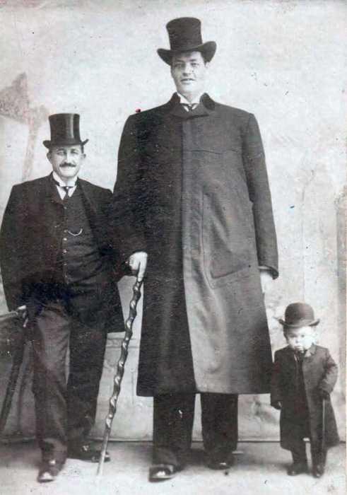 Снимок трех мужчин, которые по высоте отличаются друг от друга разным ростом.