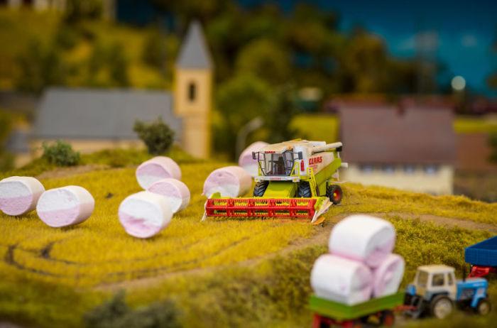 Тюки сена грузят и вывозят с помощью сельскохозяйственной техники.