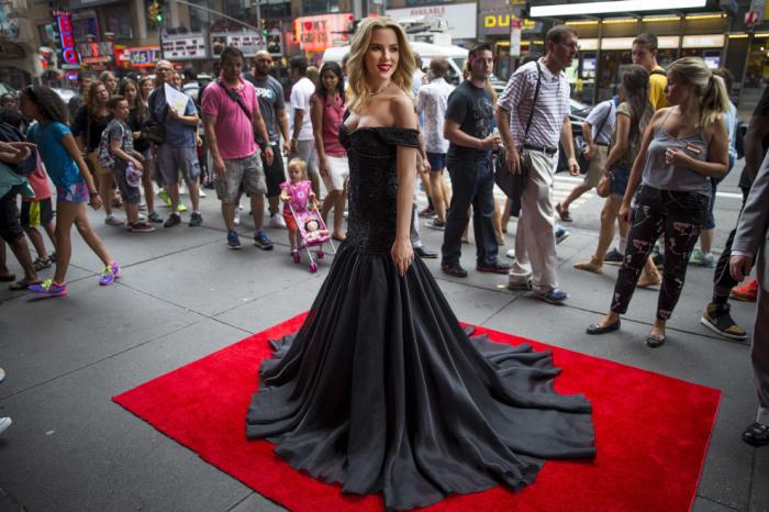 Восковая фигура прекрасной американской актрисы в черном платье «позирует» на красной дорожке.