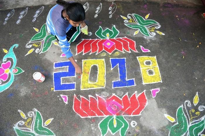 Женщина использует цветной порошок для создания ритуального новогоднего узора перед домом.