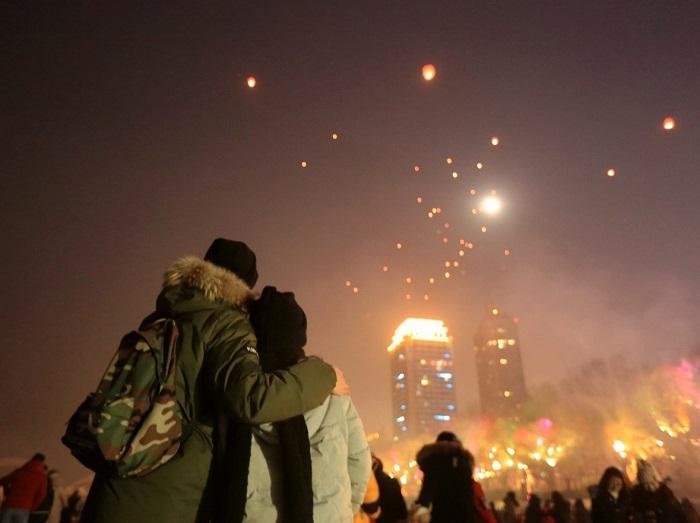 Влюбленная пара любуется яркими взлетающими небесными фонариками.
