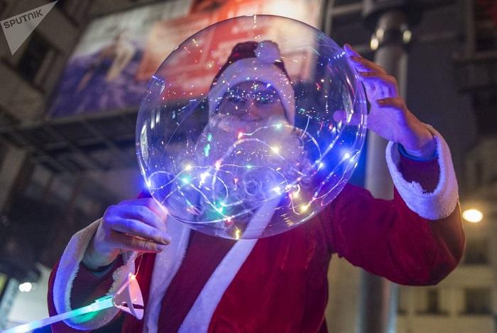 Мужчина в костюме Деда Мороза с праздничным надувным шариком.