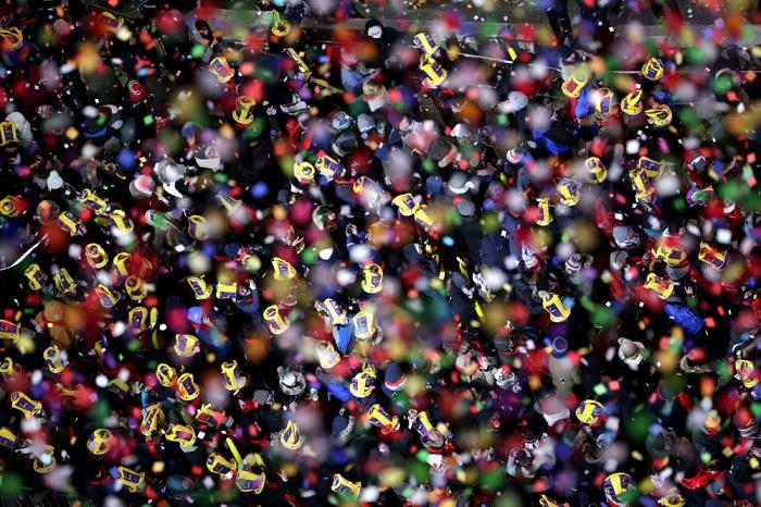 Конфетти падает на многочисленную толпу на Таймс-сквер  с первыми минутами наступившего 2018 года.