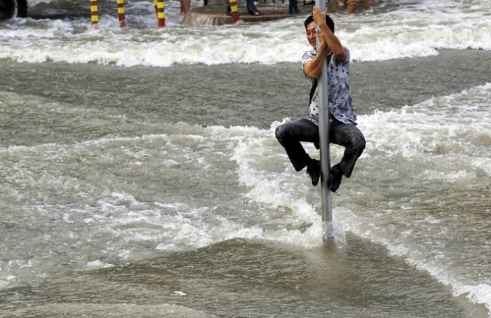 Мужчина спасается от приливной волны на реке Цяньтан, которая заполонила деревню Хангджоу.