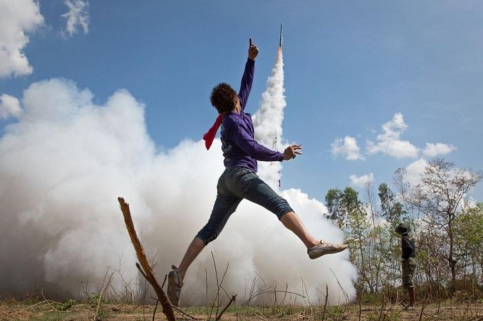 Молодой человек подпрыгивает в воздухе в знак радости на фестивале ракет Бунг Банг Фай, чтобы отпраздновать долгожданный сезон дождей, Ясотхон, Таиланд.