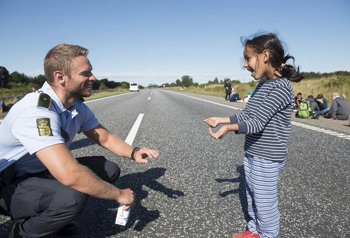 Датский полицейский играет с девочкой из семьи мигрантов, Дания.
