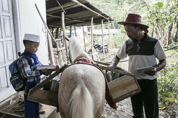 42-летний Ридван Сурури отбирает новые книги для специальной мобильной библиотеки, в то время как мальчик ищет что-то интересное, чтобы почитать, Индонезия.