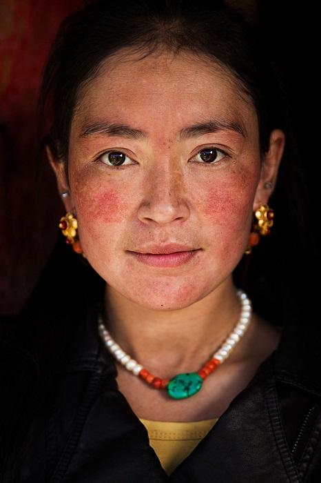Эта тибетская женщина занималась уборкой в доме, но все же носила украшения.