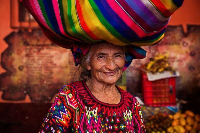 Улыбающаяся женщина переносит груз в небольшом городке Гватемалы.