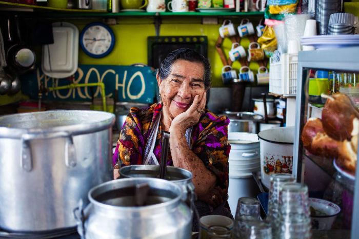 Искренняя улыбка женщины, работающей на продовольственном рынке.
