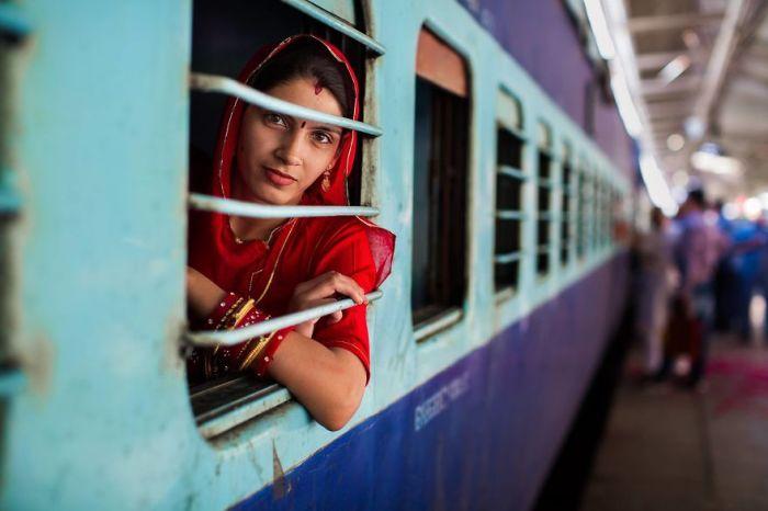 Мимолетная улыбка женщины в традиционной одежде из окна поезда, остановившегося на вокзале.
