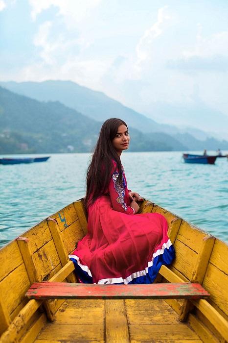 Изящная девушка проводит уик-энд, катаясь на лодке по великолепному озеру Пхева.