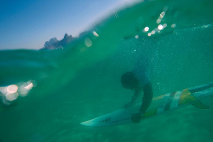 Сёрфер ныряет на мысе Арпоадор в Рио-де-Жанейро, Бразилия.