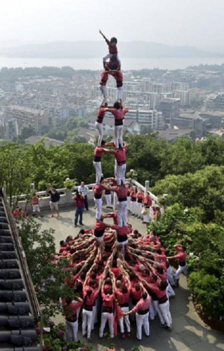 Испанские кастельеры возводят башню из людей во время представления у озера Сиху в Ханчжоу , Китай.