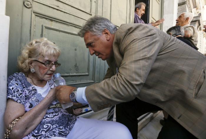 Банкир оказывает помощь пенсионерке, которой стало плохо в очереди возле Национального банка Греции в Афинах.