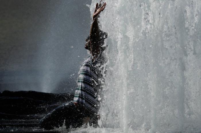 Мужчина освежается в фонтане в Берлине, Германия.