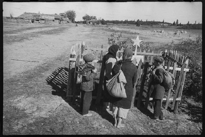 Жители освобожденной деревни Молодино на братской могиле.