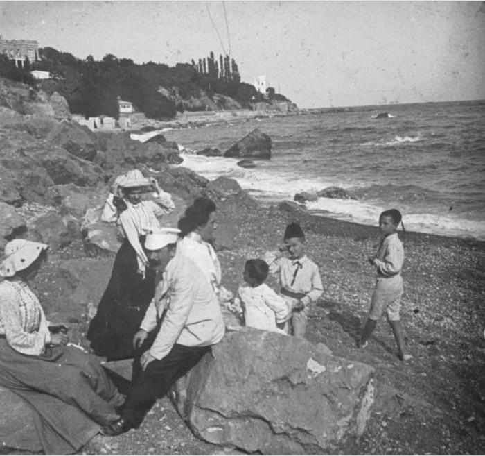 Родители с детьми наслаждаются отдыхом на побережье Черного моря.