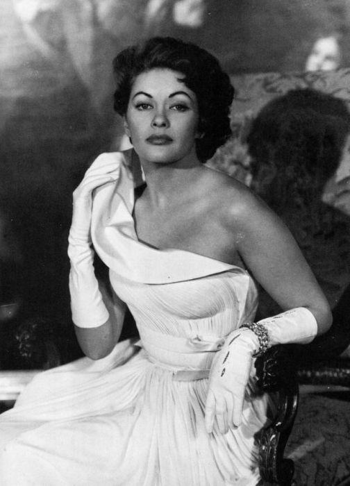 Лёгкая причёска, белые перчатки, колье на руке замечательно дополняют образ женщины.