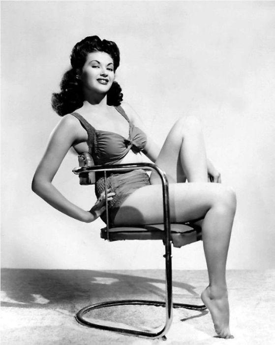 Игривый образ женщины в купальнике на стуле.
