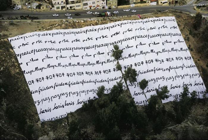 Гигантская ткань, сделанная Кларой Хелтер и развернутая на земле, с надписью «Мир», написанной на нескольких языках.