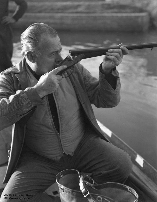 Известный американский писатель и журналист Эрнест Хемингуэй занят проверкой своего двуствольного ружья.