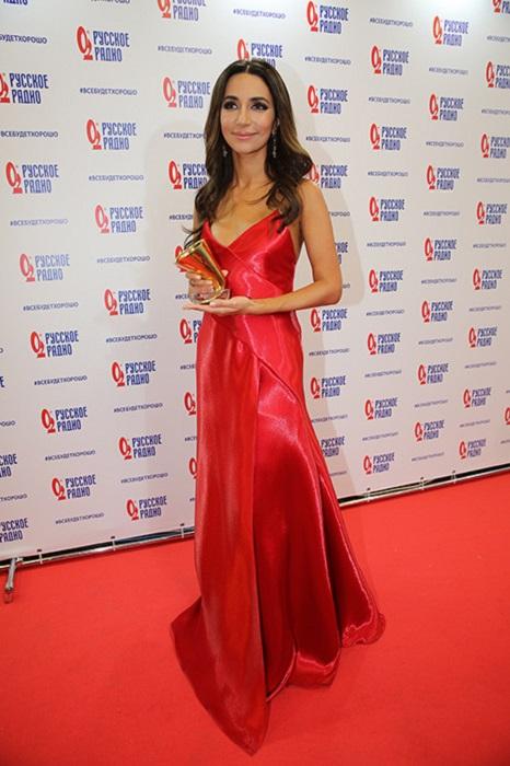 Платье насыщенного красного цвета выгодно подчеркнуло изящную фигуру певицы.