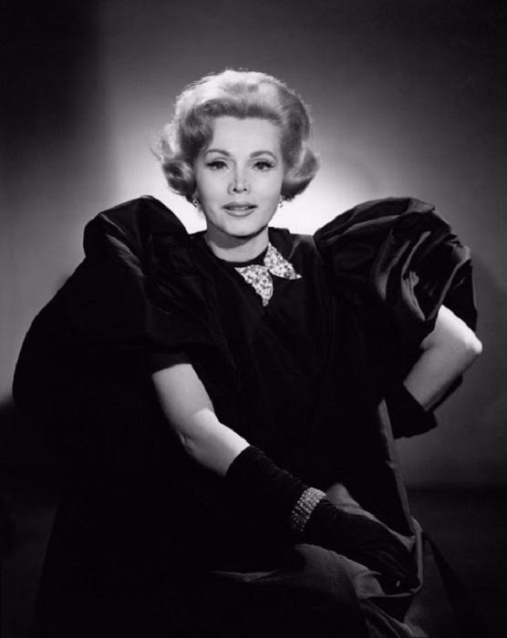 Актриса в великолепном черном платье и перчатках с бабочкой брошью.