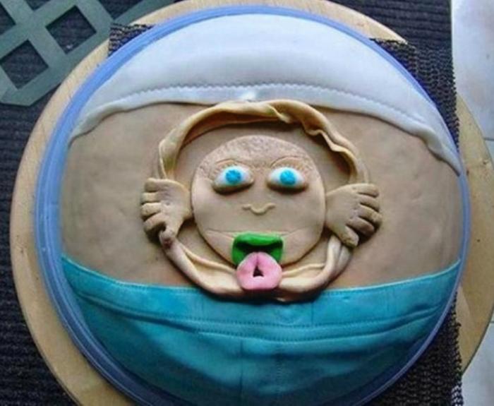 Торт в виде животика с личиком малыша.