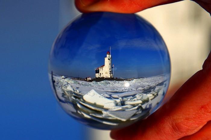 Маяк на острове Маркен, вид на достопримечательность сквозь хрустальный шар