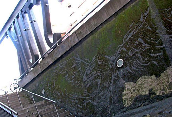 Уличное граффити, созданное напором воды на замшелой стене