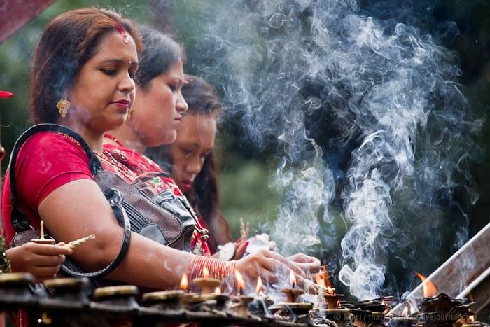 Обязательный ритуал во время празднований: женщины зажигают благовония возле храма