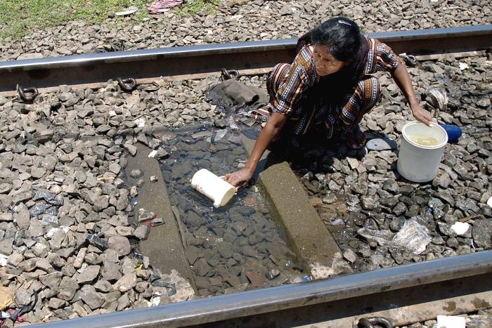 Жительница трущоб набирает воду на железнодорожных рельсах. Индия, Мумбаи.