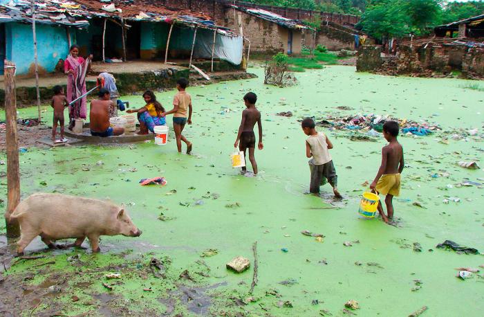 Жители трущоб набирают воду из единственной не затопленной колонки после ливней в Аллахабаде.