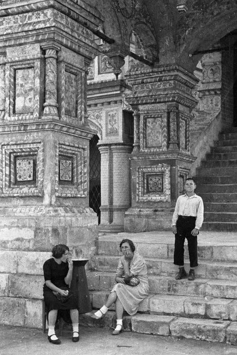 Люди, сидящие на ступеньках собора Василия Блаженного.