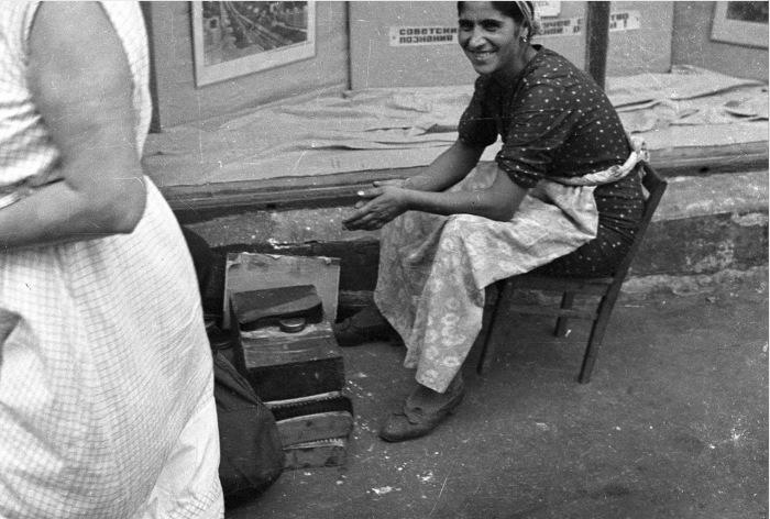 Женщина, работающая чистильщицей обуви.