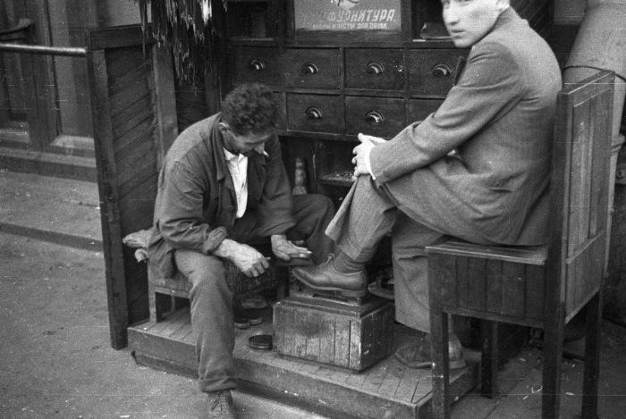 Мужчина, работающий чистильщиком обуви неподалеку от центра Москвы.