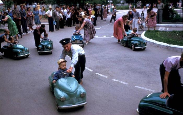 Дети, катающиеся на маленьких колесных автомобильчиках.