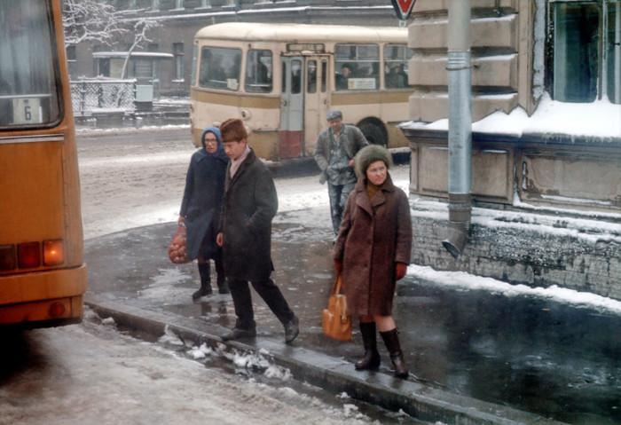 Женщина ждущая свой автобус на остановке.